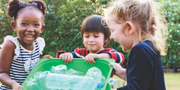 Three children with recycling bin