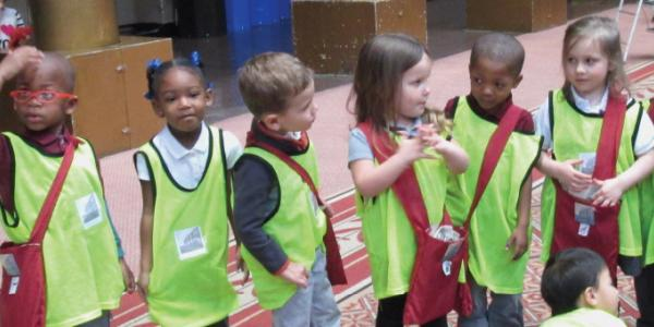 Line of small children wearing safety vests
