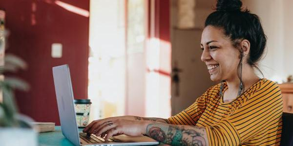 Woman at a laptop typing and smiling