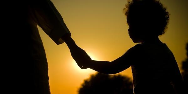 A parent holding a child's hand