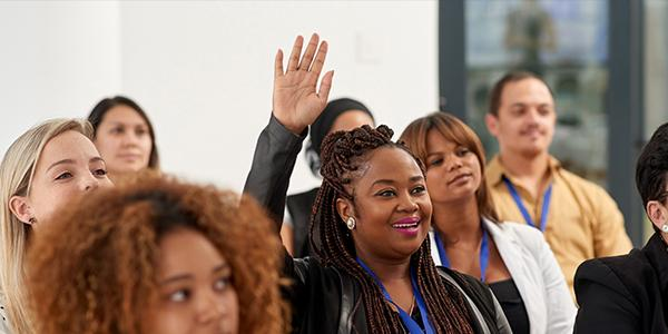 A woman in a training session raises her hand to ask a question