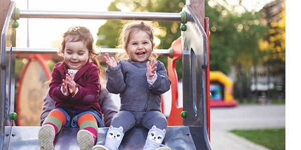 two laughing children sitting on a slide
