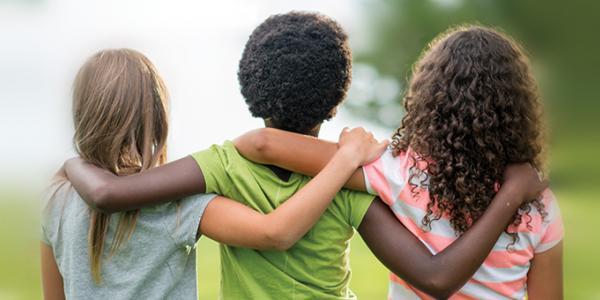 Three children hugging each other