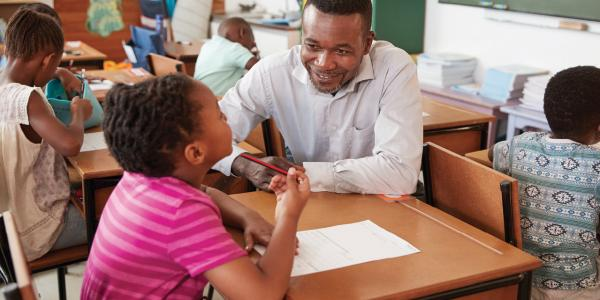 Male teacher helping student in classroom