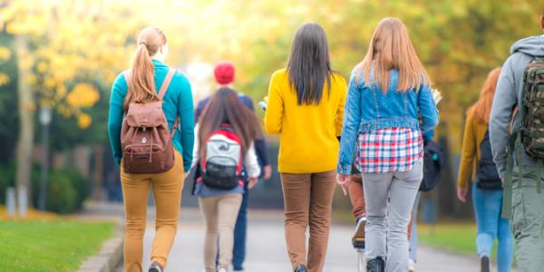 Back view of college students walking on campus