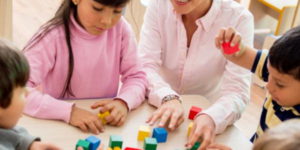 Children and teacher playing with blocks
