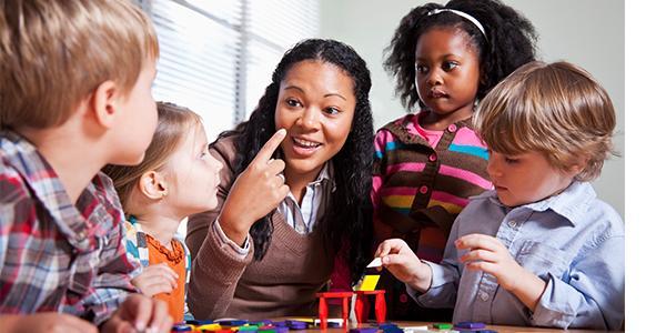 A teacher with kindergartners leading play time