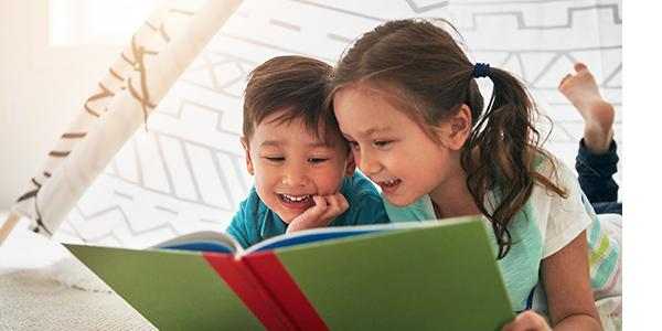 A girl and boy reading a book together