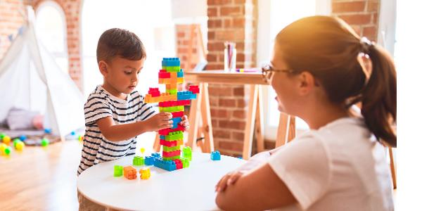 Teacher and preschooler building with colored blocks