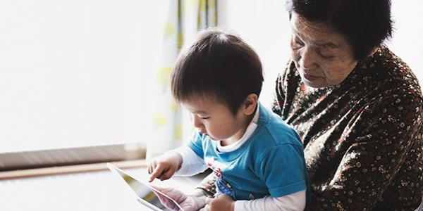 Preschool boy in his grandma's lap, learning on a tablet