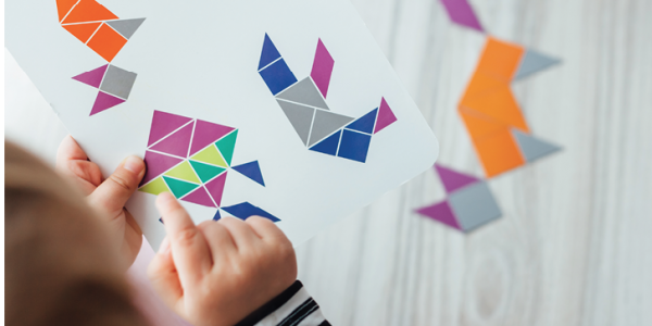 A young child copies designs of various geometric shapes on a piece of paper.
