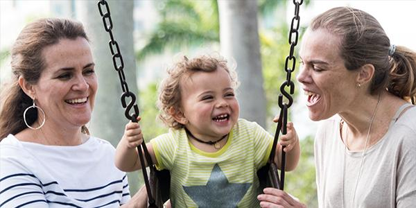 Two adults play with a young child on a swing