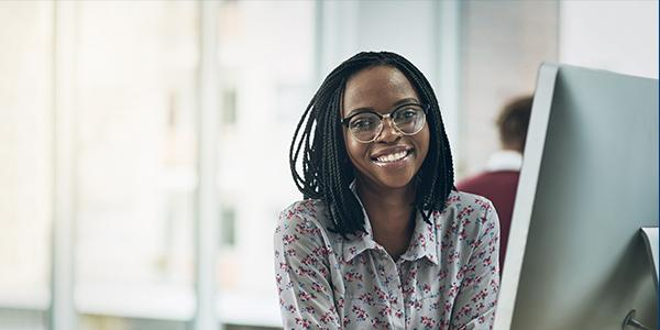 A woman behind a desktop smiles at the camera