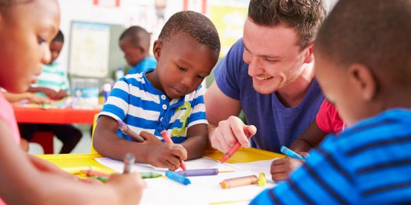 Male teacher sitting at a table with preschool children as they color