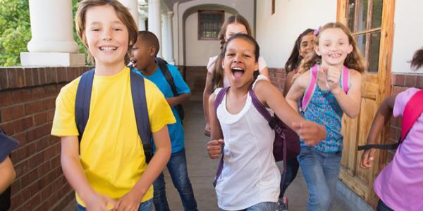 Children wearing backpacks in school hallway