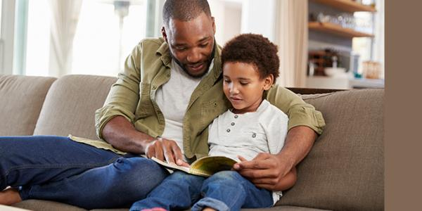 Dad and son reading a book on the couch