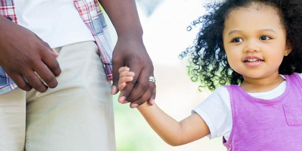 Young girl holding an adult's hand