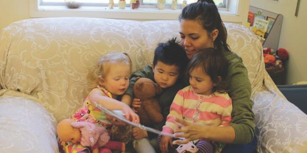 Teacher reading a children's book to three toddlers