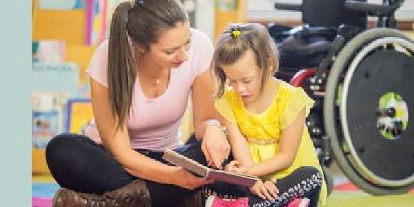 Teacher helping child read a book