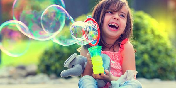 Child plays with bubbles outside