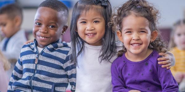 three children sitting and smiling