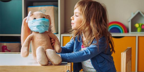 little girl playing with doll and putting a mask on