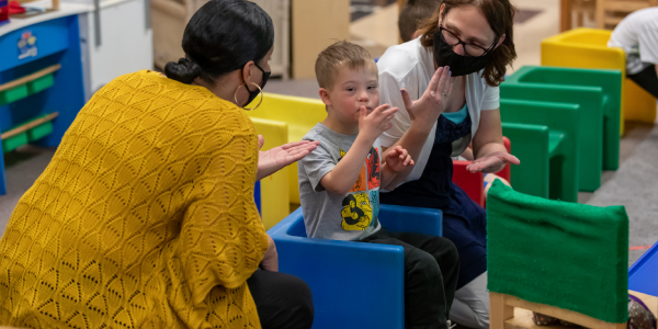 two teachers in face masks making hand gestures with a child