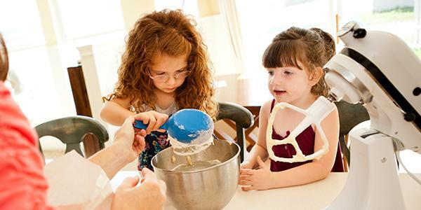 Two young girls baking with a parent