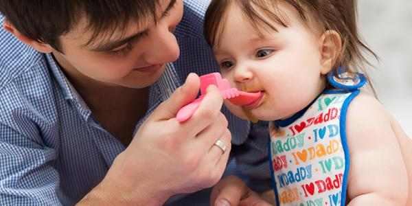Male family child care provider feeding an infant