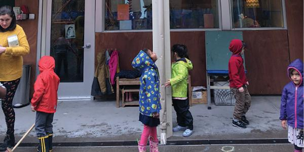 Children standing outside in rain