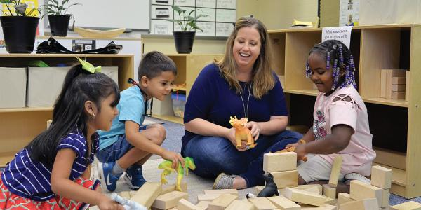 Teacher and students playing with dinosaurs and blocks in the classroom