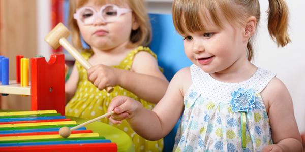 Two toddlers playing with xylophone