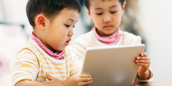Two toddlers looking at tablet