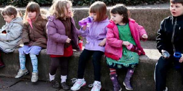 Children sitting on sidewalk