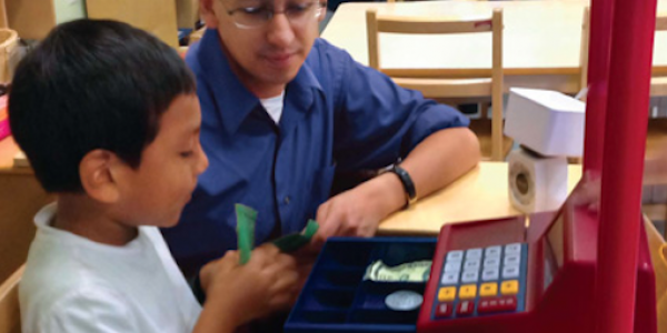 Teacher and student using a toy cash register