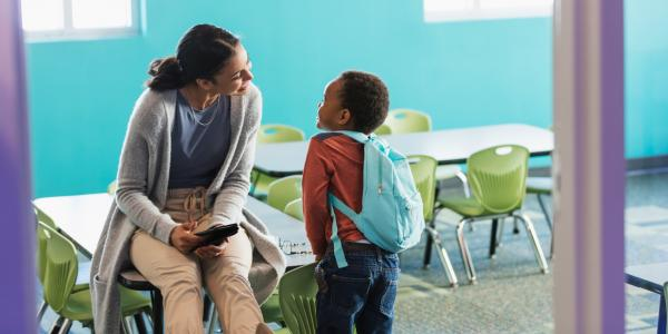 A teacher converses with her student.