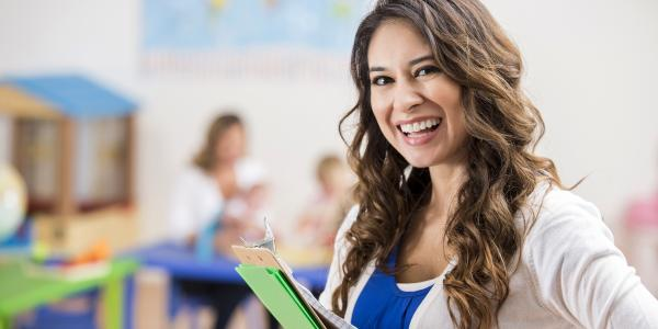 Woman in a classroom holding file folders