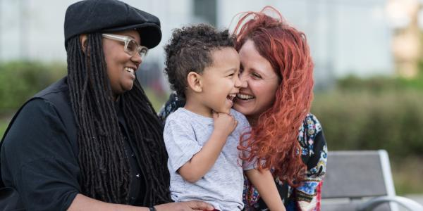 Two women interacting with a male toddler.