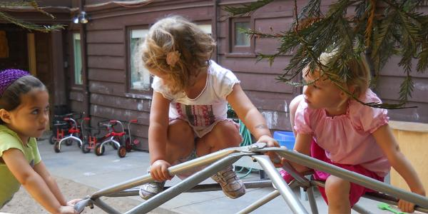 Three little girls playing together outside.