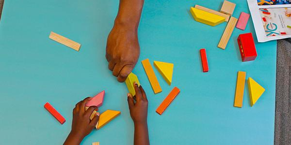 Teacher playing blocks with student.