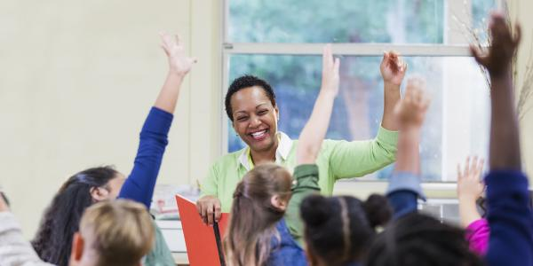 Teacher raising hand with students
