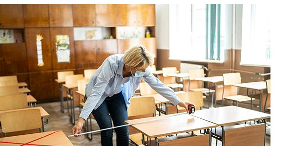 Educator measuring the distance between desk in classroom