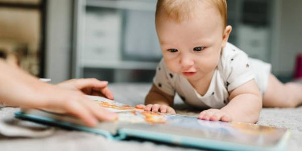 A baby on the floor with a book.