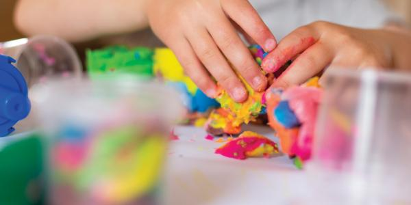 child's hands kneading playdough