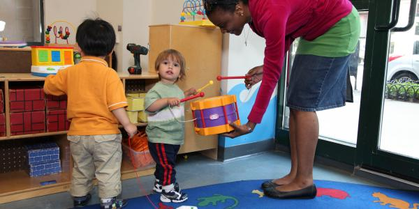 Toddlers in a learning environment playing with female teacher.