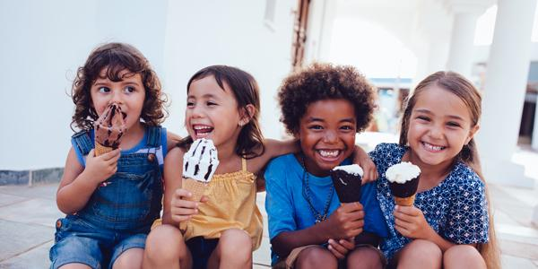 Group of diverse young children eating ice cream