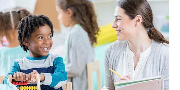 Teacher and preschool boy smiling in a classroom