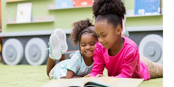 Two preschool girls on the floor in the classroom reading a book together
