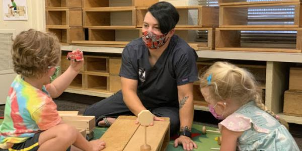 Teaching in a classroom with two children, playing with blocks.