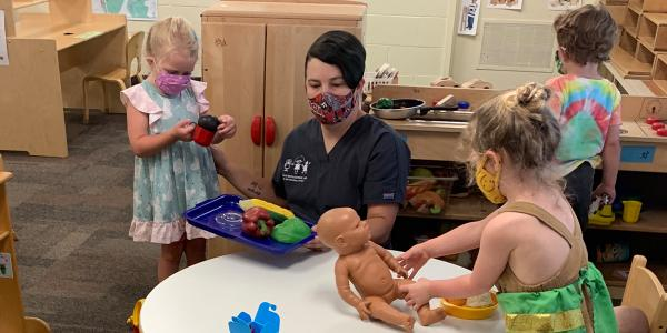 Teacher in a classroom with three young children, all wearing masks.